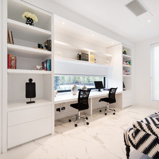 This is an example of a large contemporary study room in Melbourne with white walls, a built-in desk and grey floor.