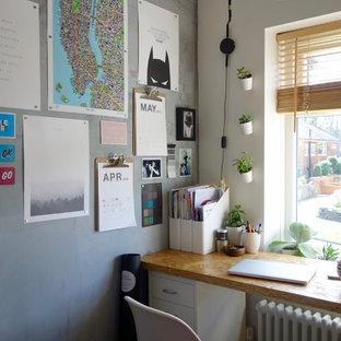 Idéer för små funkis hemmabibliotek, med grå väggar och ett fristående skrivbord