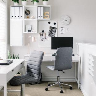 エドモントンの北欧スタイルのおしゃれな書斎 (白い壁、カーペット敷き、暖炉なし、自立型机、ベージュの床) の写真