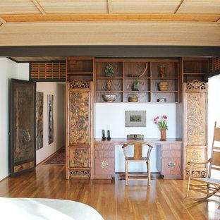 ロサンゼルスの大きいアジアンスタイルのおしゃれなホームオフィス・書斎 (ベージュの壁、淡色無垢フローリング、造り付け机、暖炉なし、茶色い床) の写真