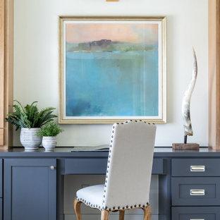 Inspiration för stora lantliga hemmabibliotek, med vita väggar, ljust trägolv, en standard öppen spis, en spiselkrans i betong, ett inbyggt skrivbord och brunt golv