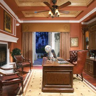 Esempio di uno studio tradizionale con pareti rosse, parquet scuro, camino classico e scrivania autoportante