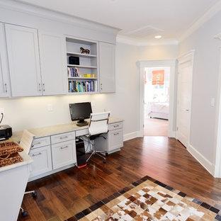 Mittelgroßes Klassisches Arbeitszimmer ohne Kamin mit braunem Holzboden, Einbau-Schreibtisch, Studio, blauer Wandfarbe und braunem Boden in Raleigh