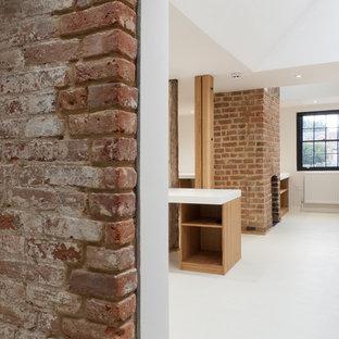 ロンドンの大きいモダンスタイルのおしゃれなホームオフィス・書斎 (マルチカラーの壁、リノリウムの床、標準型暖炉、レンガの暖炉まわり、造り付け机、白い床) の写真