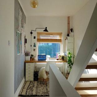 На фото: маленькое рабочее место в скандинавском стиле с белыми стенами, ковровым покрытием и отдельно стоящим рабочим столом без камина с