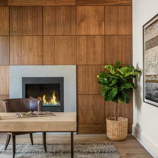 Exempel på ett modernt hemmabibliotek, med vita väggar, ljust trägolv, en spiselkrans i betong, ett fristående skrivbord, en standard öppen spis och beiget golv
