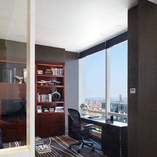 ニューヨークの大きいコンテンポラリースタイルのおしゃれな書斎 (グレーの壁、カーペット敷き、自立型机、暖炉なし、黒い床) の写真