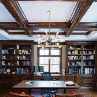На фото: кабинет в стиле кантри с библиотекой, серыми стенами, темным паркетным полом, угловым камином и отдельно стоящим рабочим столом с