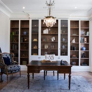 Exempel på ett klassiskt hemmabibliotek, med beige väggar, mellanmörkt trägolv, ett fristående skrivbord och brunt golv