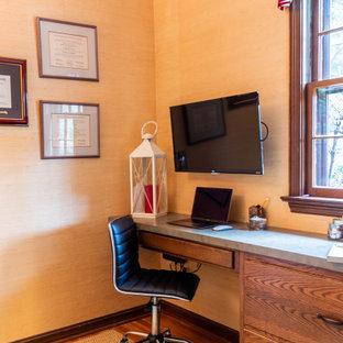 Foto de despacho tradicional, pequeño, con paredes amarillas, suelo de madera en tonos medios, escritorio empotrado y suelo marrón