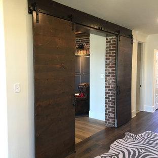 Mittelgroßes Industrial Arbeitszimmer ohne Kamin mit Arbeitsplatz, roter Wandfarbe, hellem Holzboden, freistehendem Schreibtisch und beigem Boden in Austin