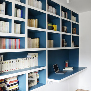 Photo of a contemporary home office and library in Other with white walls, medium hardwood flooring, a built-in desk and brown floors.