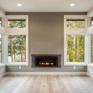 Foto de despacho rural con paredes beige, suelo de madera clara, chimeneas suspendidas y marco de chimenea de piedra