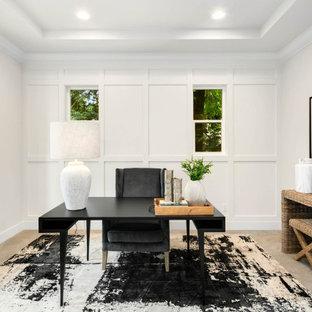 Lantlig inredning av ett mellanstort arbetsrum, med vita väggar, heltäckningsmatta, ett fristående skrivbord och grått golv