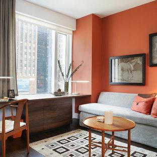 Foto di uno studio minimal con pareti arancioni e scrivania incassata