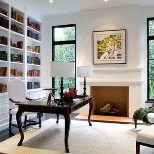 ロサンゼルスの地中海スタイルのおしゃれなホームオフィス・仕事部屋 (白い壁、濃色無垢フローリング、標準型暖炉、自立型机、黒い床) の写真