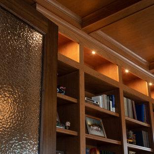 Idéer för ett stort maritimt hemmabibliotek, med bruna väggar, mellanmörkt trägolv, ett fristående skrivbord och brunt golv