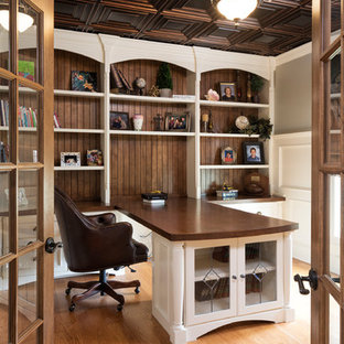 Medium sized traditional home office and library in Chicago with grey walls, medium hardwood flooring, a built-in desk and brown floors.