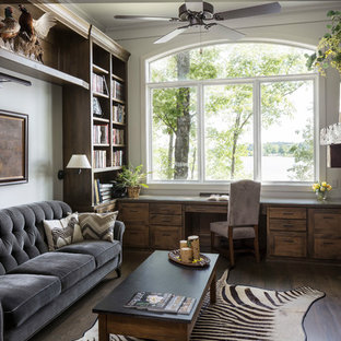 Immagine di un ufficio stile rurale con pareti bianche, parquet scuro, camino classico, cornice del camino in pietra, scrivania incassata e pavimento marrone