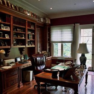Inspiration för stora klassiska arbetsrum, med röda väggar, mörkt trägolv och ett fristående skrivbord