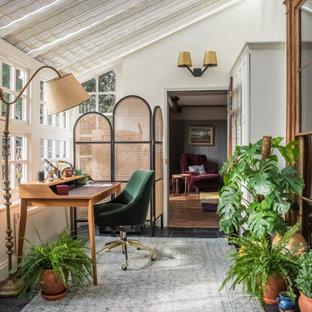 Inspiration för mellanstora eklektiska hemmabibliotek, med skiffergolv, svart golv, vita väggar och ett fristående skrivbord