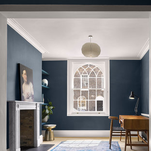 Photo of a traditional home office and library in London with blue walls, light hardwood flooring, a standard fireplace, a stone fireplace surround, a freestanding desk and beige floors.