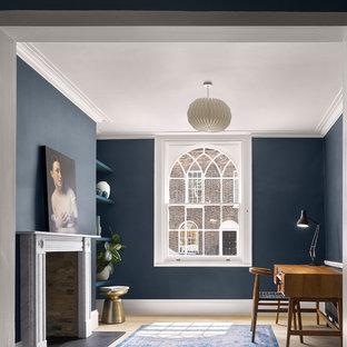 ロンドンのトランジショナルスタイルのおしゃれなホームオフィス・仕事部屋 (青い壁、淡色無垢フローリング、標準型暖炉、石材の暖炉まわり、自立型机、ベージュの床) の写真