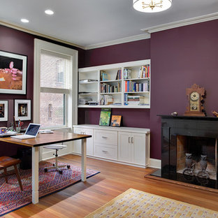 Large traditional home office in New York with purple walls, medium hardwood flooring, a standard fireplace, a stone fireplace surround and a freestanding desk.