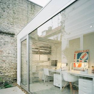 Inredning av ett modernt stort arbetsrum, med vita väggar, betonggolv och ett fristående skrivbord