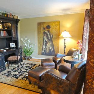 Imagen de despacho clásico, pequeño, sin chimenea, con paredes amarillas, suelo de madera en tonos medios, escritorio independiente y suelo marrón