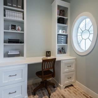 Inredning av ett klassiskt litet arbetsrum, med grå väggar, tegelgolv och ett inbyggt skrivbord