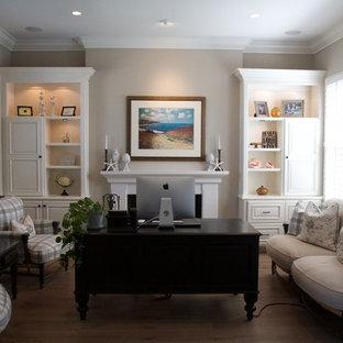 Foto di un ufficio classico di medie dimensioni con pareti grigie, parquet chiaro, camino classico, cornice del camino in cemento e scrivania autoportante