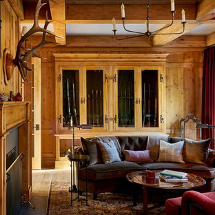 Mid-sized elegant medium tone wood floor and brown floor study room photo in Denver with brown walls, a standard fireplace and a wood fireplace surround