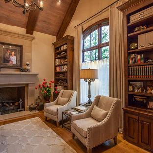 Immagine di un grande ufficio classico con pareti beige, pavimento in legno massello medio, camino classico, scrivania incassata e cornice del camino in intonaco