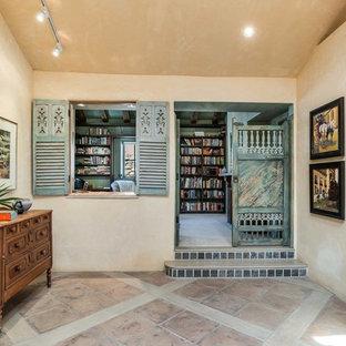 На фото: домашняя библиотека среднего размера в стиле фьюжн с желтыми стенами, ковровым покрытием, стандартным камином, фасадом камина из штукатурки, отдельно стоящим рабочим столом и бежевым полом