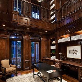 Immagine di un ampio studio tradizionale con libreria, pareti marroni, parquet scuro, scrivania autoportante e nessun camino