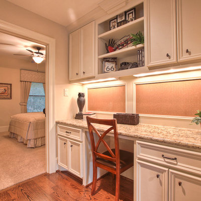 Home office - traditional built-in desk dark wood floor home office idea in Houston with beige walls