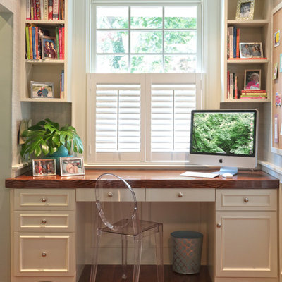 Example of a classic built-in desk medium tone wood floor home office design in Other with white walls