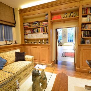Foto di uno studio tradizionale di medie dimensioni con libreria, parquet scuro e cornice del camino in mattoni