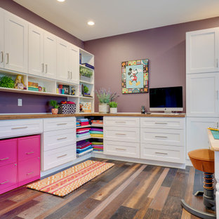 Design ideas for a large classic craft room in Seattle with purple walls, dark hardwood flooring, no fireplace, a built-in desk and brown floors.