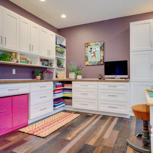 Diseño de sala de manualidades tradicional renovada, grande, sin chimenea, con paredes púrpuras, suelo de madera oscura, escritorio empotrado y suelo marrón