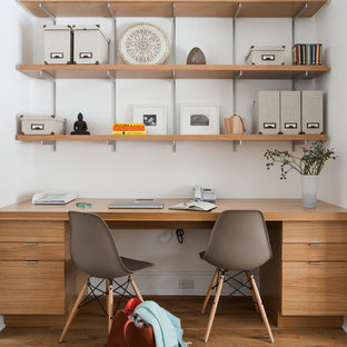 Inspiration for a mid-sized transitional freestanding desk medium tone wood floor study room remodel in Auckland with white walls