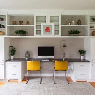ボストンの中サイズのトランジショナルスタイルのおしゃれなホームオフィス・仕事部屋 (造り付け机、茶色い床、グレーの壁、無垢フローリング) の写真