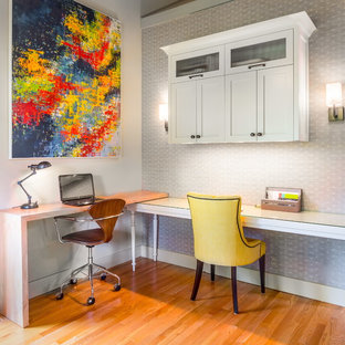Study room - mid-sized transitional built-in desk medium tone wood floor study room idea in Seattle with gray walls