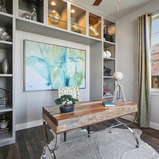 Mittelgroßes Klassisches Arbeitszimmer mit Arbeitsplatz, grauer Wandfarbe, dunklem Holzboden, freistehendem Schreibtisch und braunem Boden in Dallas