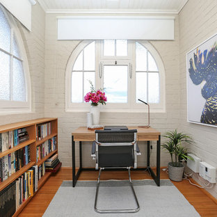 Foto de despacho clásico renovado, pequeño, sin chimenea, con paredes blancas, suelo de madera en tonos medios y escritorio independiente