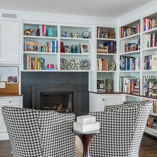 Modelo de despacho clásico renovado, de tamaño medio, con paredes verdes, suelo de madera oscura, chimenea tradicional, marco de chimenea de metal, escritorio empotrado y suelo marrón