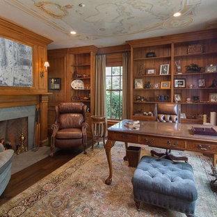Mittelgroßes Klassisches Arbeitszimmer mit Arbeitsplatz, brauner Wandfarbe, dunklem Holzboden, Kamin, Kaminumrandung aus Beton, freistehendem Schreibtisch und braunem Boden in New York