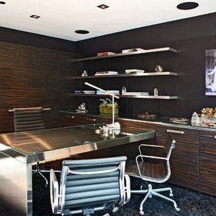 Foto på ett stort funkis hemmabibliotek, med svarta väggar, ett inbyggt skrivbord, travertin golv och beiget golv