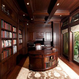 Esempio di un grande studio tradizionale con libreria, pareti rosse, pavimento in legno massello medio, nessun camino, scrivania autoportante e pavimento rosso